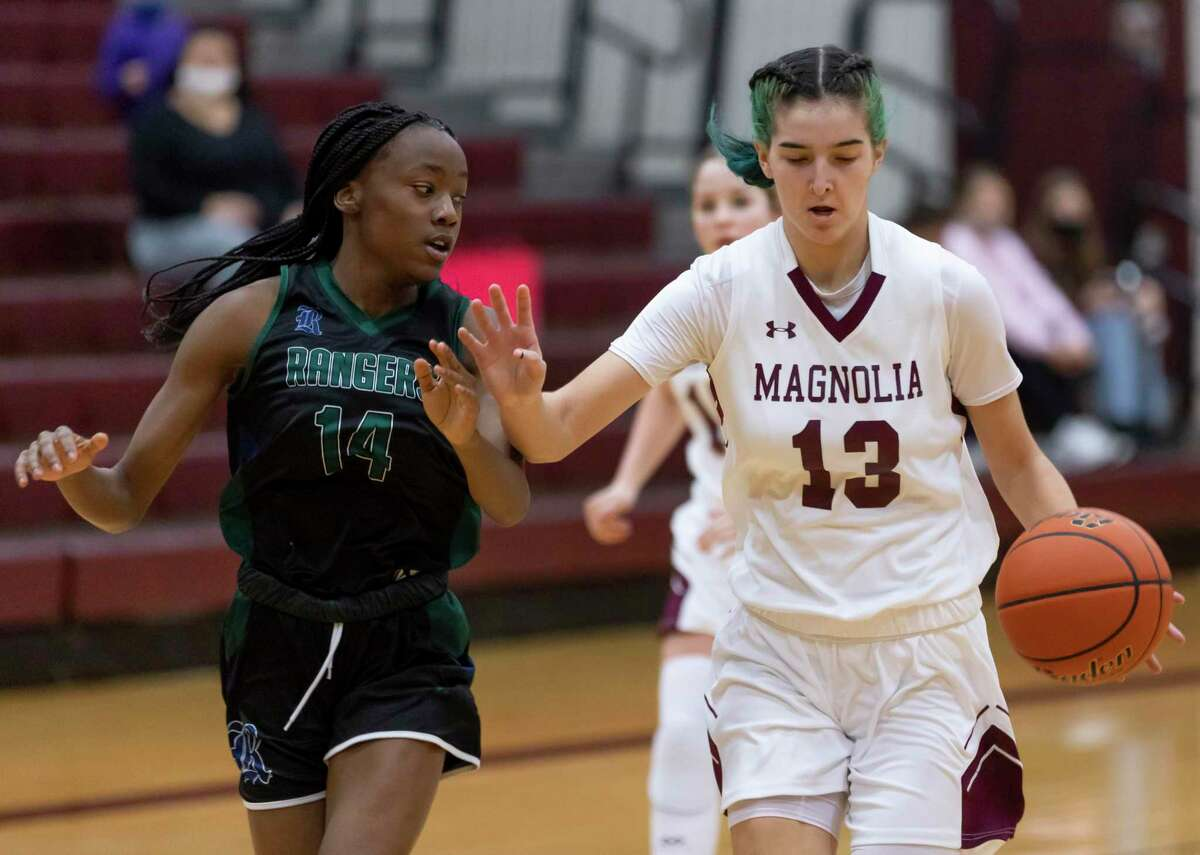 Magnolia forward Gabrielle Huetter (13) dribbles the ball down the court while pressured from Bryan Rudder Asani McGee (14) during the second quarter of a District 19-5A girls basketball game at Magnolia High School, Tuesday, Jan 12, 2021, in Magnolia.