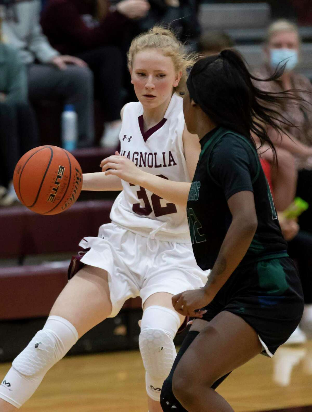 Magnolia guard Emma Rowan (32) drives the ball while under pressure from Bryan Rudder Bryanna Turner (12) during the first quarter of a District 19-5A girls basketball game at Magnolia High School, Tuesday, Jan 12, 2021, in Magnolia.