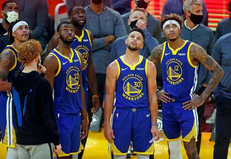 Golden State Warriors' Damion Lee, Andrew Wiggins, Draymond Green, Stephen Curry, Steve Kerr and Kelly Oubre, Jr. watch replay during Indiana Pacers' 104-95 win during NBA game at Chase Center in San Francisco, Calif., on Tuesday, January 12, 2021.