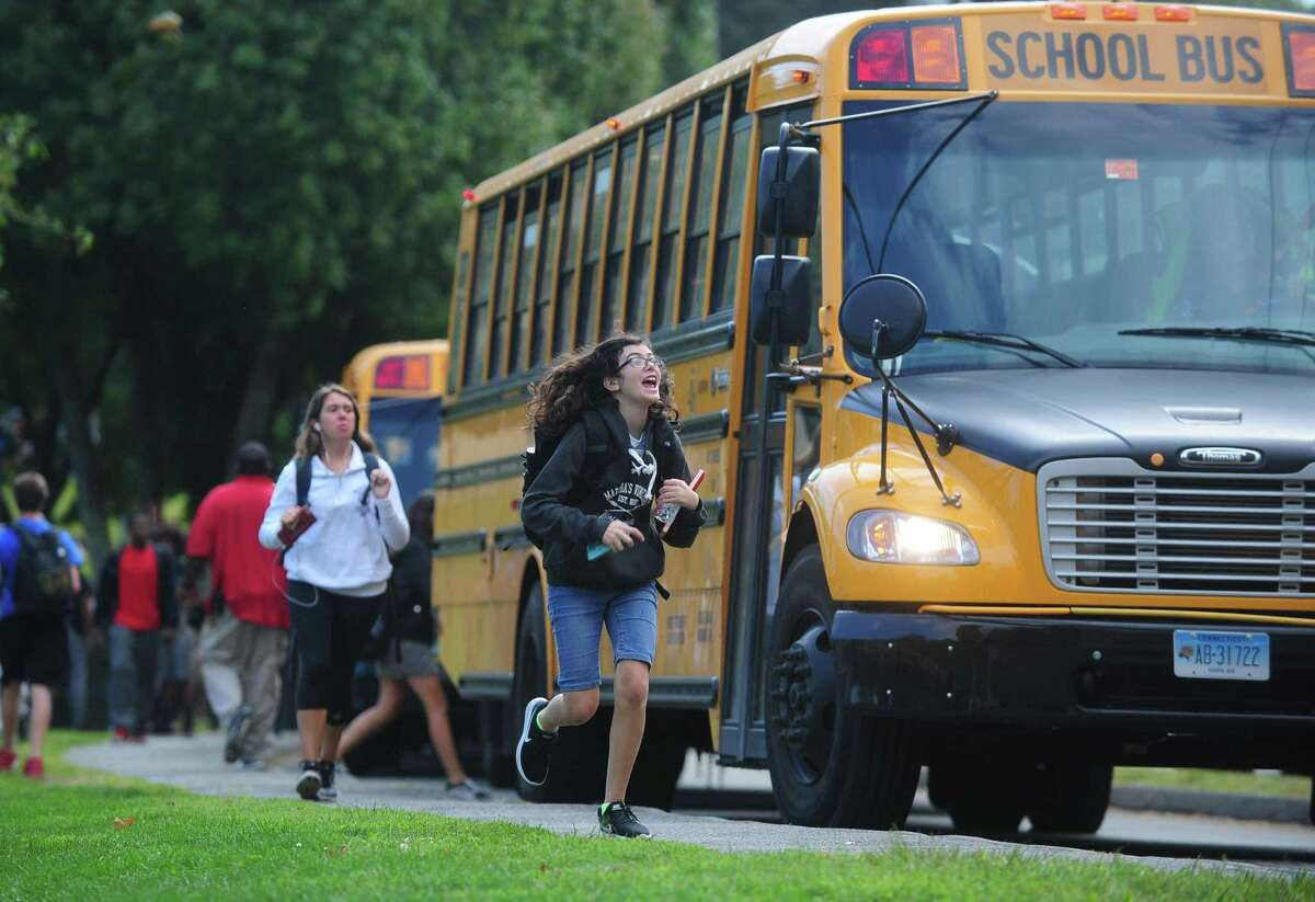 Norwalk High School students catch their First Student buses after school Friday, September 15, 2017, in Norwalk, Conn.