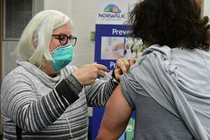 Volunteer Patricia Carey administers the new COVID vaccine to an employee of Silver Hills senior residence as Lt. Governor Bysiewicz, Norwalk Mayor Harry Rilling, Norwalk Department of Health Director Deanna D'Amore, and state Rep. Stephanie Thomas tour a vaccination clinic at the Norwalk Senior Center Friday, January 8, 2021, in Norwalk, Conn. The Norwalk Health Department has vaccinated more than 200 people eligible under Phase 1A. The Norwalk Health Department received its first shipment of Moderna's COVID-19 vaccine on Wednesday, Dec. 23, 2020.