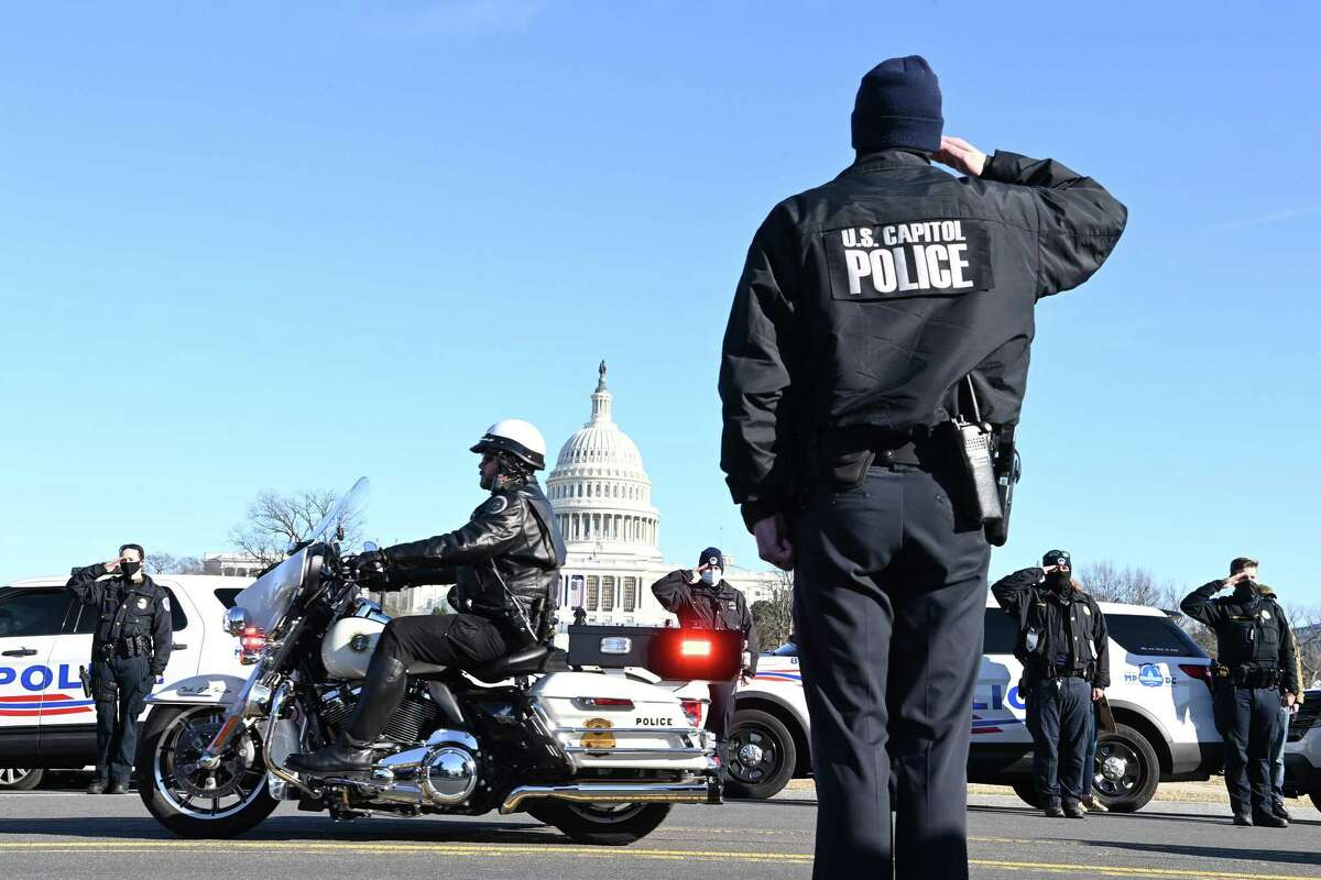 Officers salute during the procession for U.S. Capitol Police Officer Brian Sicknick in Washington on Jan. 10.