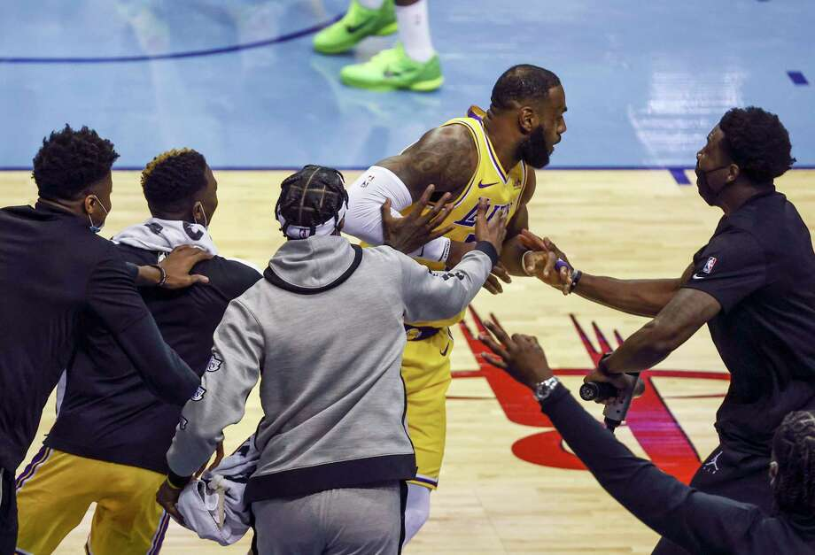 The Los Angeles Lakers bench mobs LeBron James after he hit a no-look 3-pointer right in front of them during the second quarter of their win against the Rockets on Tuesday at Toyota Center. Photo: Troy Taormina, Associated Press / Troy Taormina