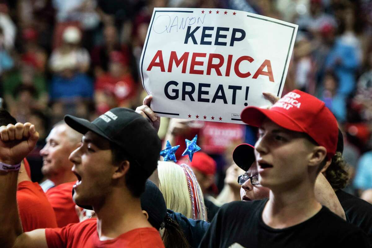 Supporters cheer with a QAnon sign as President Donald Trump prepares to speak at a