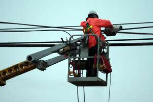 Hydro worker in a boom bucket performs maintenance on a power line.