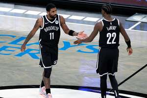 Kyrie Irving high-fives Caris LeVert of the Brooklyn Nets during the first half against the Golden State Warriors at Barclays Center on December 22, 2020 in the Brooklyn borough of New York City.