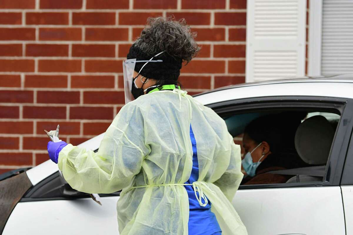 A health care worker gathers paperwork from a driver at the drive-through COVID-19 testing site at the Whitney Young Administrative Building on Wednesday, Jan. 13, 2021 in Watervliet, N.Y. (Lori Van Buren/Times Union)