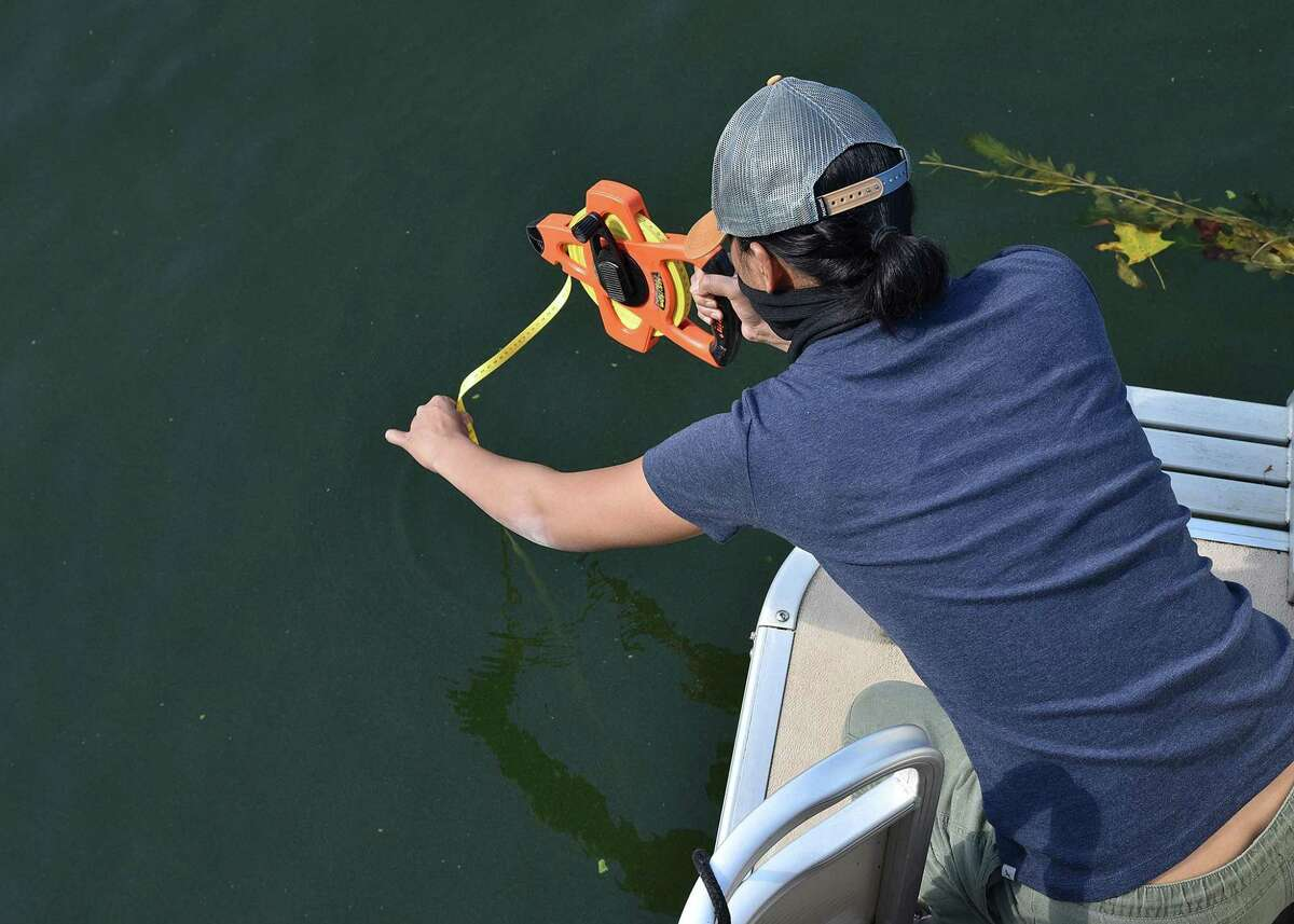 WCSU graduate student Maricris Rivera of New Britain measures the water depth at a site during sample collections.