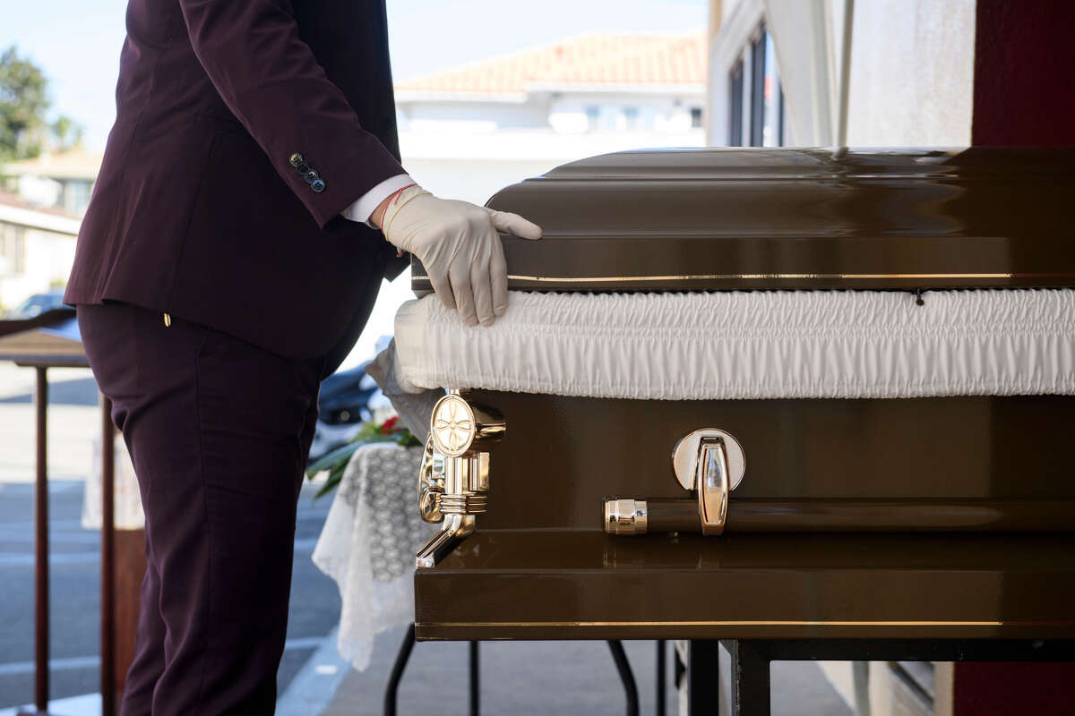 Funeral director Steven Correa wears gloves as he moves the casket of Gilberto Arreguin Camacho, 58, in preparation for burial following his death due to Covid-19 at Continental Funeral Home on New Year's Eve, December 31, 2020.