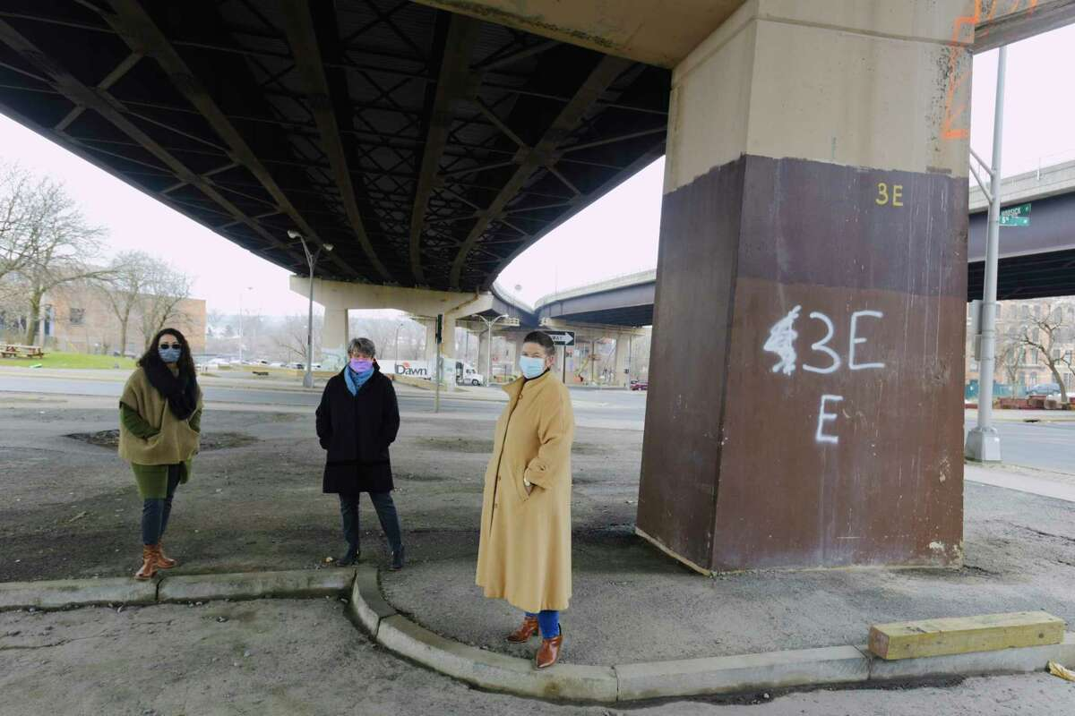 Belinda Colon, left, curator at the Arts Center of the Capital Region, Barbara Nelson, center, with TAP inc., and Elizabeth Reiss, head of the Arts Center of the Capital Region, pose for a photo under the Hoosick St. bridge on Wednesday, Jan. 13, 2021, in Troy, N.Y. The Arts Center of the Capital Region is looking for proposals from area artists to create a piece of artwork that would use the surface of the bridge support structures to create the artwork on. (Paul Buckowski/Times Union)