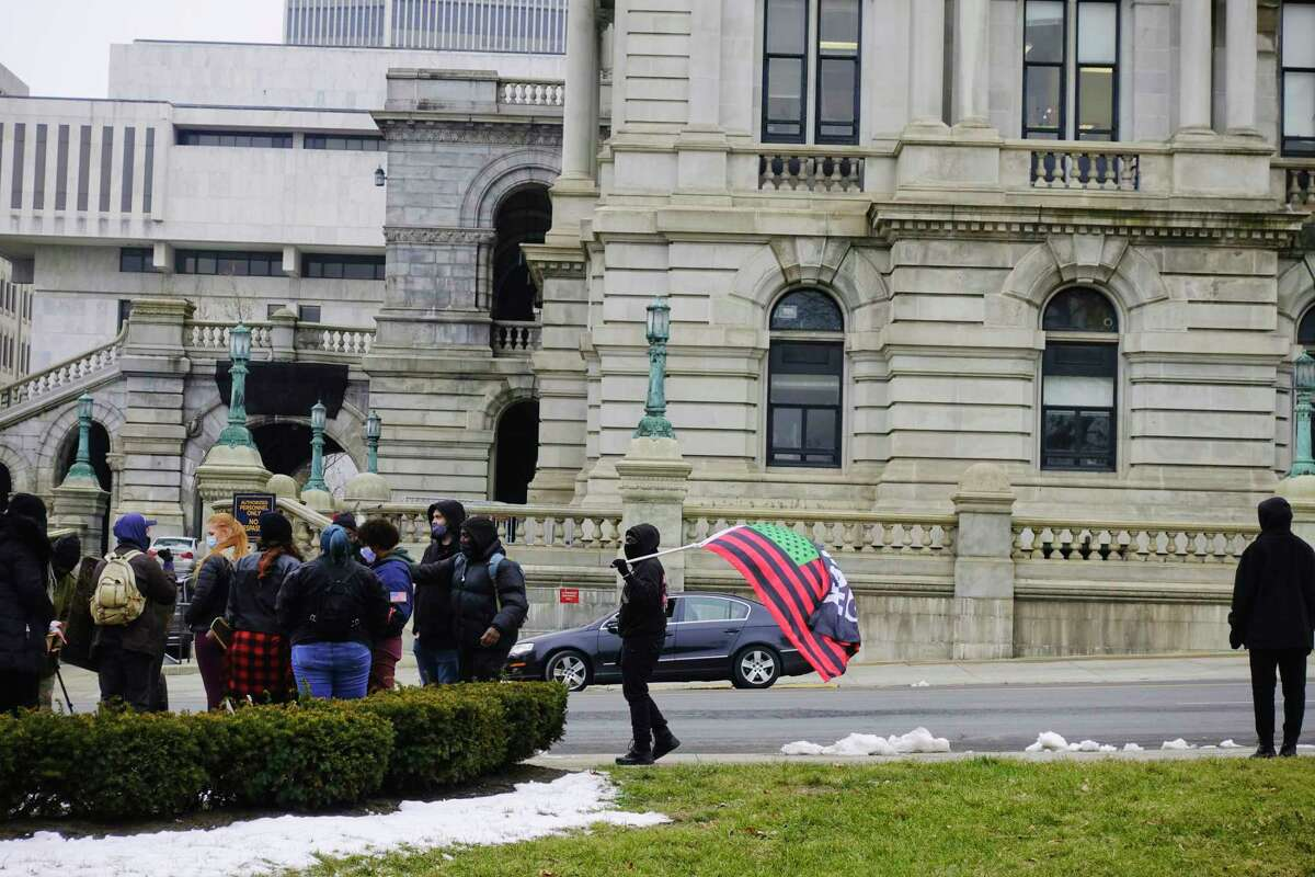 Members of the group All of Us take part in a protest outside the Capitol on Wednesday, Jan. 13, 2021, in Albany, N.Y. The group held the protest to highlight what they say are examples of police brutality. (Paul Buckowski/Times Union)