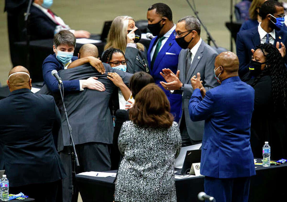 State Rep. Justin Slaughter is swarmed after a criminal justice reform bill passes the Illinois House during a lame-duck session Wednesday.