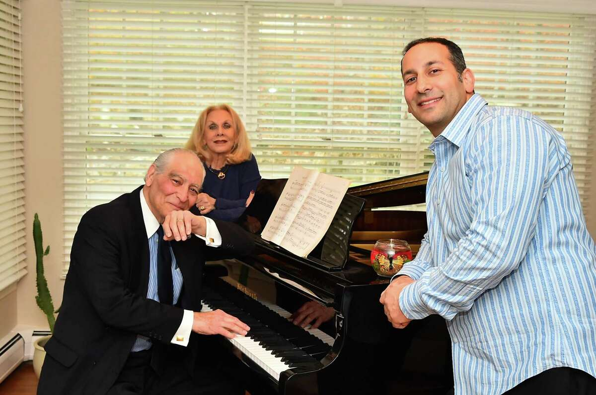 Harris L. Kligman (left) sits with his piano with wife, Nancy, and son, Rob. Kligman and his son have started to publish his extensive back catalogue of spy thrillers through Amazon and plan for more release dates in the coming weeks and months.