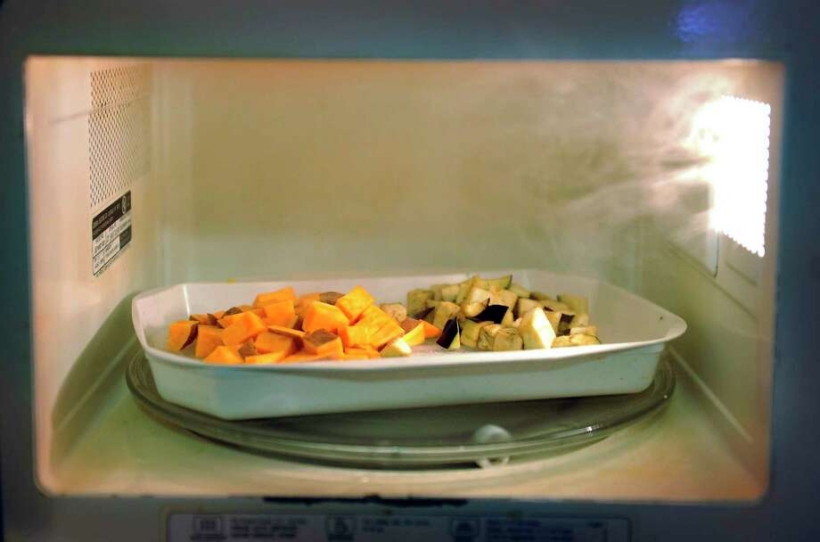 Steam comes off a microwavable steamer tray holding sweet potato and eggplant. Photo: Washington Post Photo By Matt McClain / The Washington Post