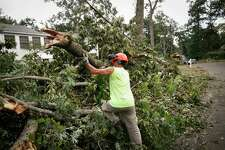 In this Aug. 7, 2020 file photo, work crews clear storm debris amid deactivated power lines in Westport, Conn. Tropical Storm Isaias packed more of a punch than many were expecting when it hit Connecticut on Aug. 4, 2020, knocking out power to more than 700,00 customers statewide.