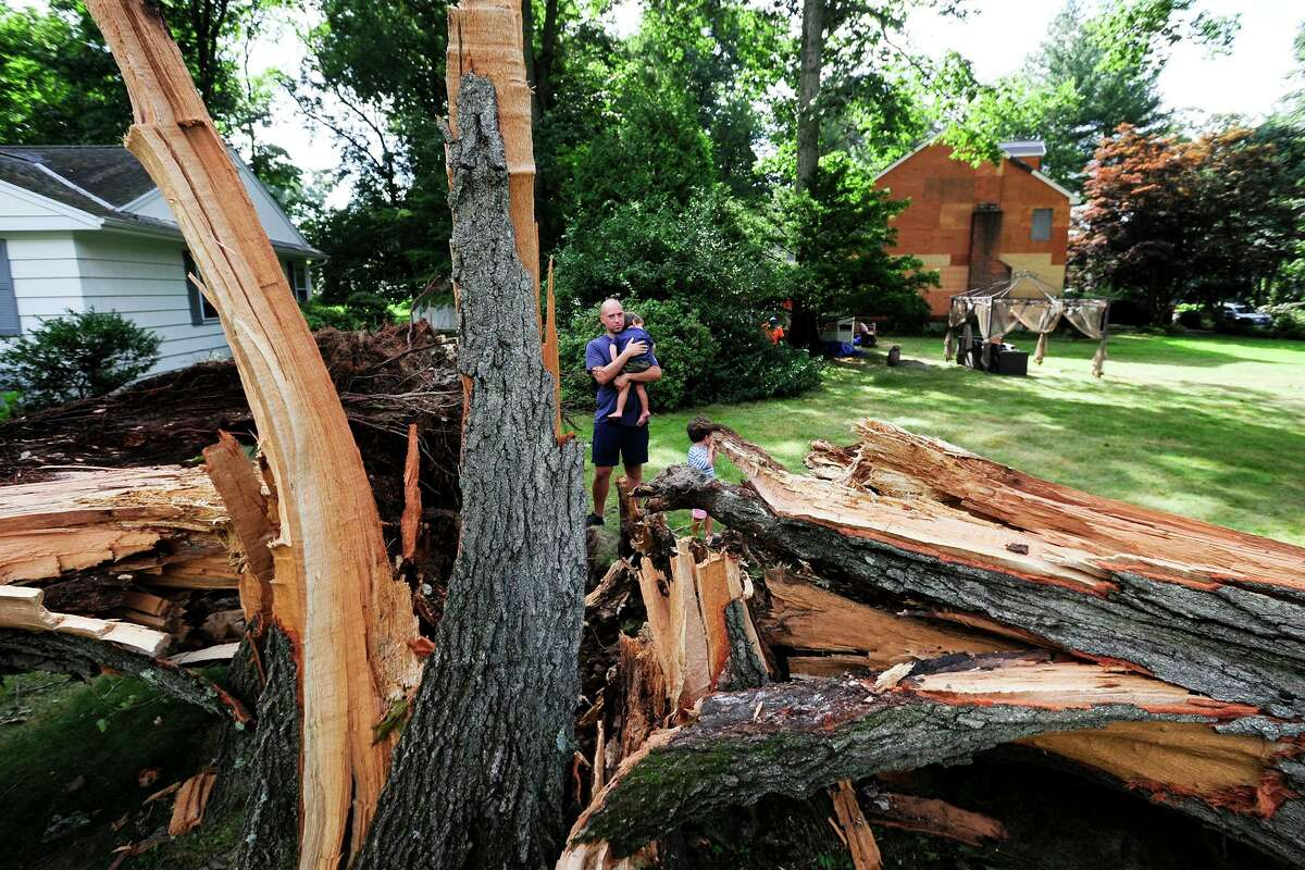 A resident holds his son near a tree that fell in front of his Bertmor Drive home in Stamford, Conn., during Tropical Storm Isaias in August 2020.