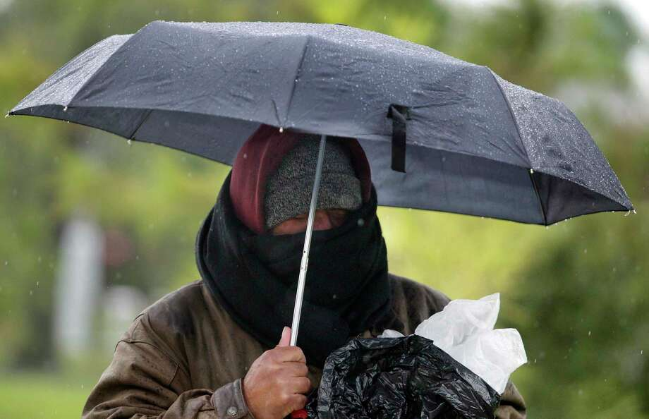 Reynaldo Cisneros Jr. attempts to stay warm during his walk in Hermann Park on a wet chilly morning on Friday, Jan. 6, 2017, in Houston. ( J. Patric Schneider / For the Chronicle ) Photo: J. Patric Schneider, Freelance / For The Chronicle / © 2017 Houston Chronicle