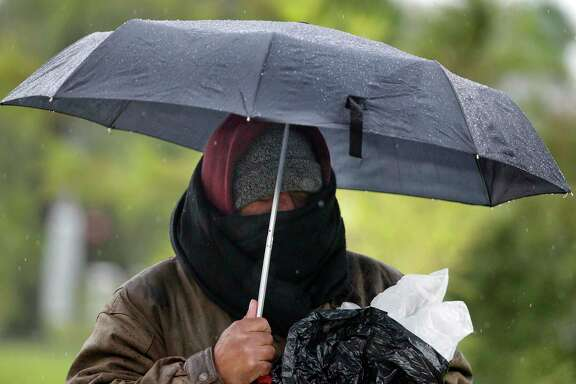 Reynaldo Cisneros Jr. attempts to stay warm during his walk in Hermann Park on a wet chilly morning on Friday, Jan. 6, 2017, in Houston. ( J. Patric Schneider / For the Chronicle )