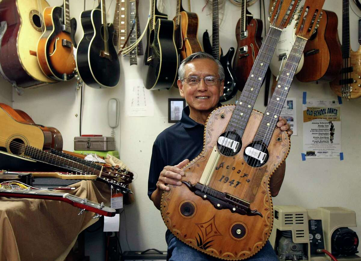 Mike Acosta, pictured at Acosta Music Co. in 2011, shows off a double-neck bajo sexto and guitar built by his father, Miguel. Mike Acosta, who ran the renowned family business until his retirement a few years ago, died Jan. 5 at age 81.