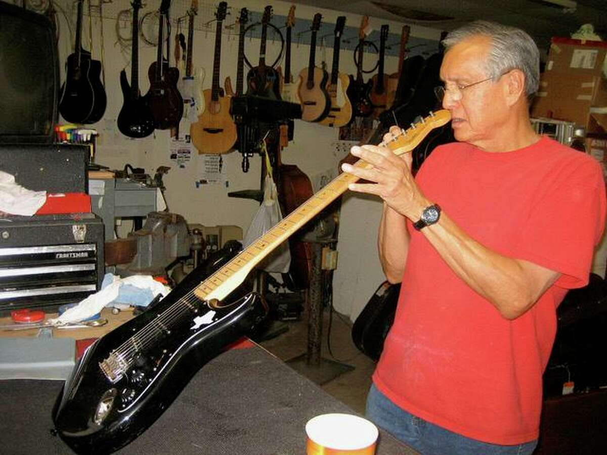 Mike Acosta works on a guitar at the Bandera Road shop.
