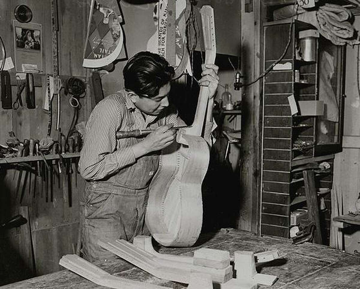 Miguel Acosta, Miguel Acosta Jr.'s father, works on a guitar in the shop at the original Acosta Music Co. store downtown.