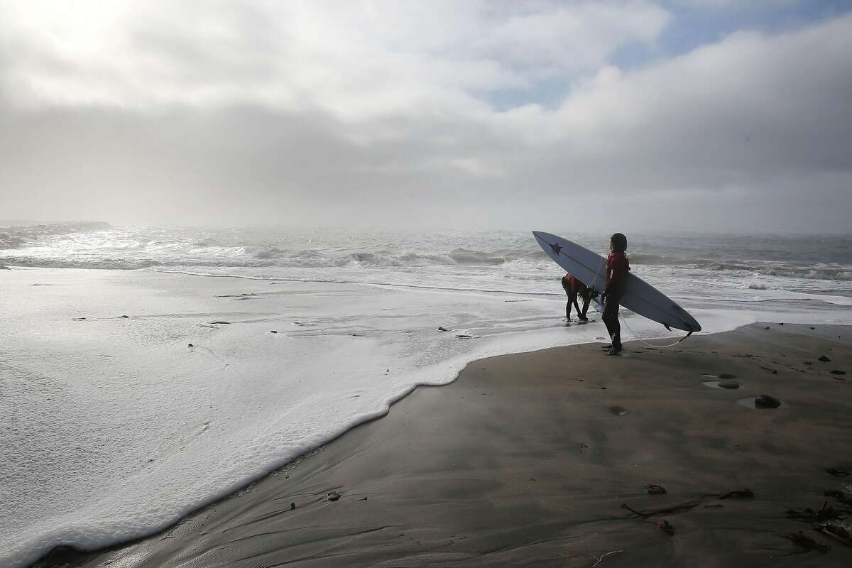 Beck Adler (front to back) of Venice and Rolando Stanley of Pascuales, Mexico. stand on Mavericks Beach as a wave rushes up the beach.