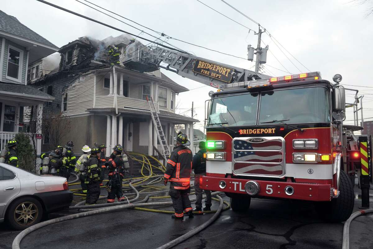 Firefighters at the scene of a fire in a multi-family home on Vine St., in Bridgeport, Conn. Jan. 13, 2021.