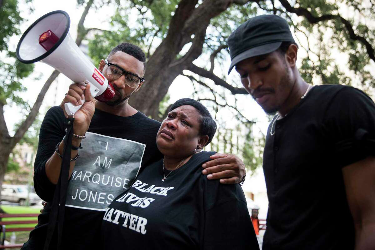 Deborah Bush, aunt of Marquise Jones who was killed by police, cries while Mike Lowe, left, and Johnathan-David Jones speak during a rally organaized by the Black Lives Matter movement before the San Antonio City Council meeting on August 31, 2016.