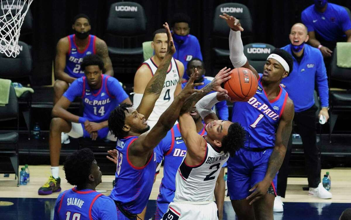 Connecticut guard James Bouknight (2) shoots against DePaul forward Pauly Paulicap (33) during the first half of an NCAA college basketball game Wednesday, Dec. 30, 2020, in Storrs, Conn. (David Butler II/Pool Photo via AP)