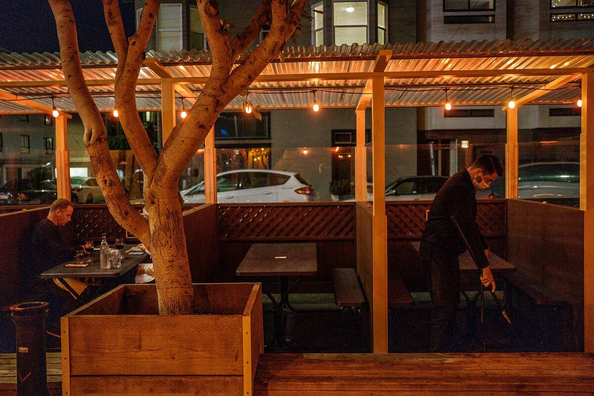 Ronnie Selak sweeps the parklet at Brazen Head in San Francisco.