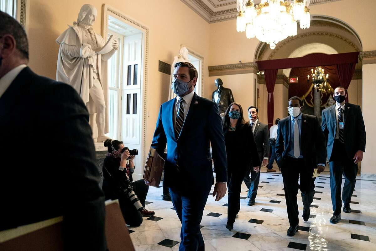 House Impeachment Manager Rep. Eric Swalwell (D-CA) (C) wears a protective mask while walking to the House Floor during a vote on the impeachment of President Donald Trump at the U.S. Capitol on January 13, 2021 in Washington, DC.