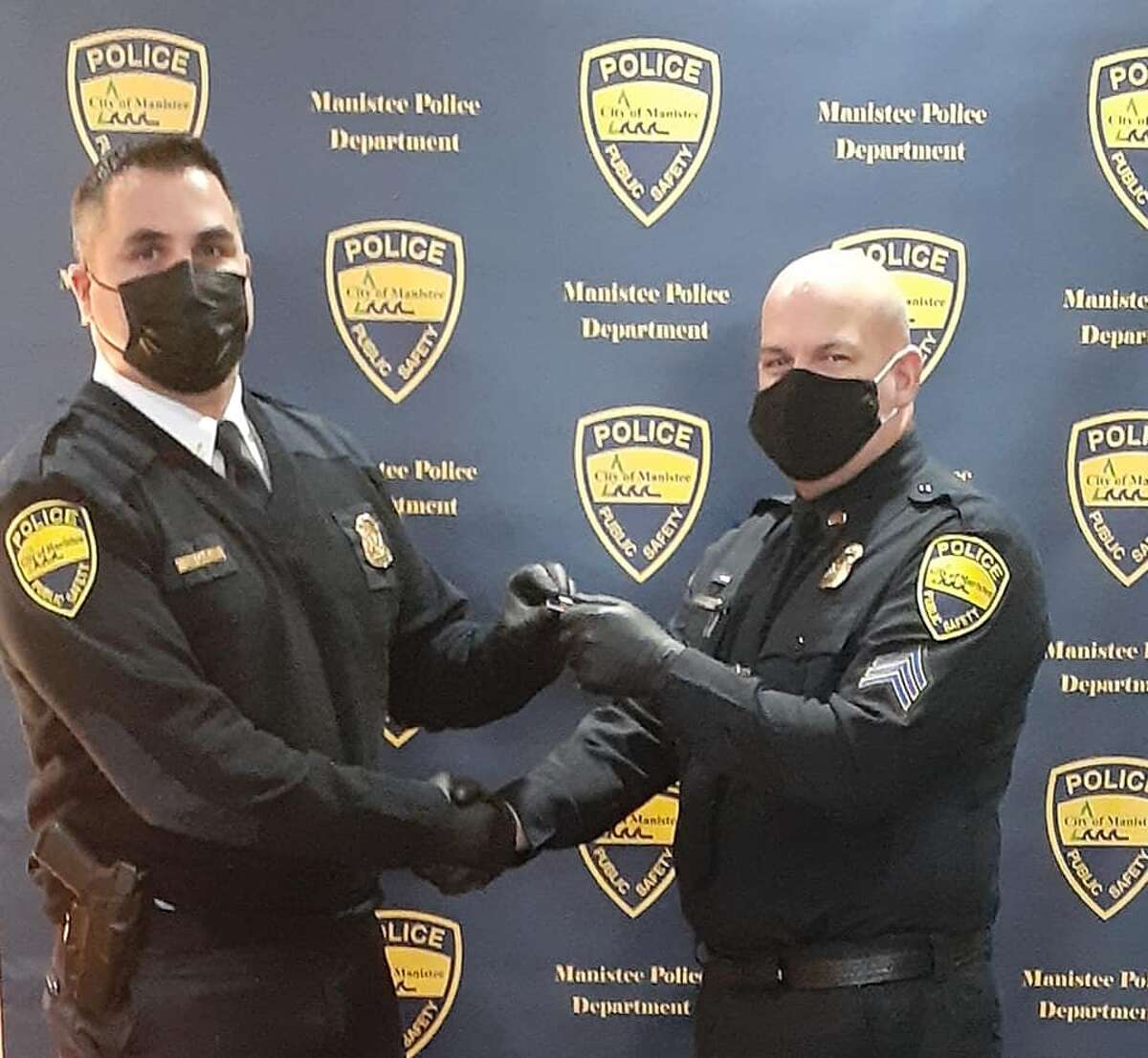 Manistee City Police Chief Josh Glass shakes hands with Sgt. Doug VanSickle's during a promotional ceremony at Manistee City Hall on Monday.