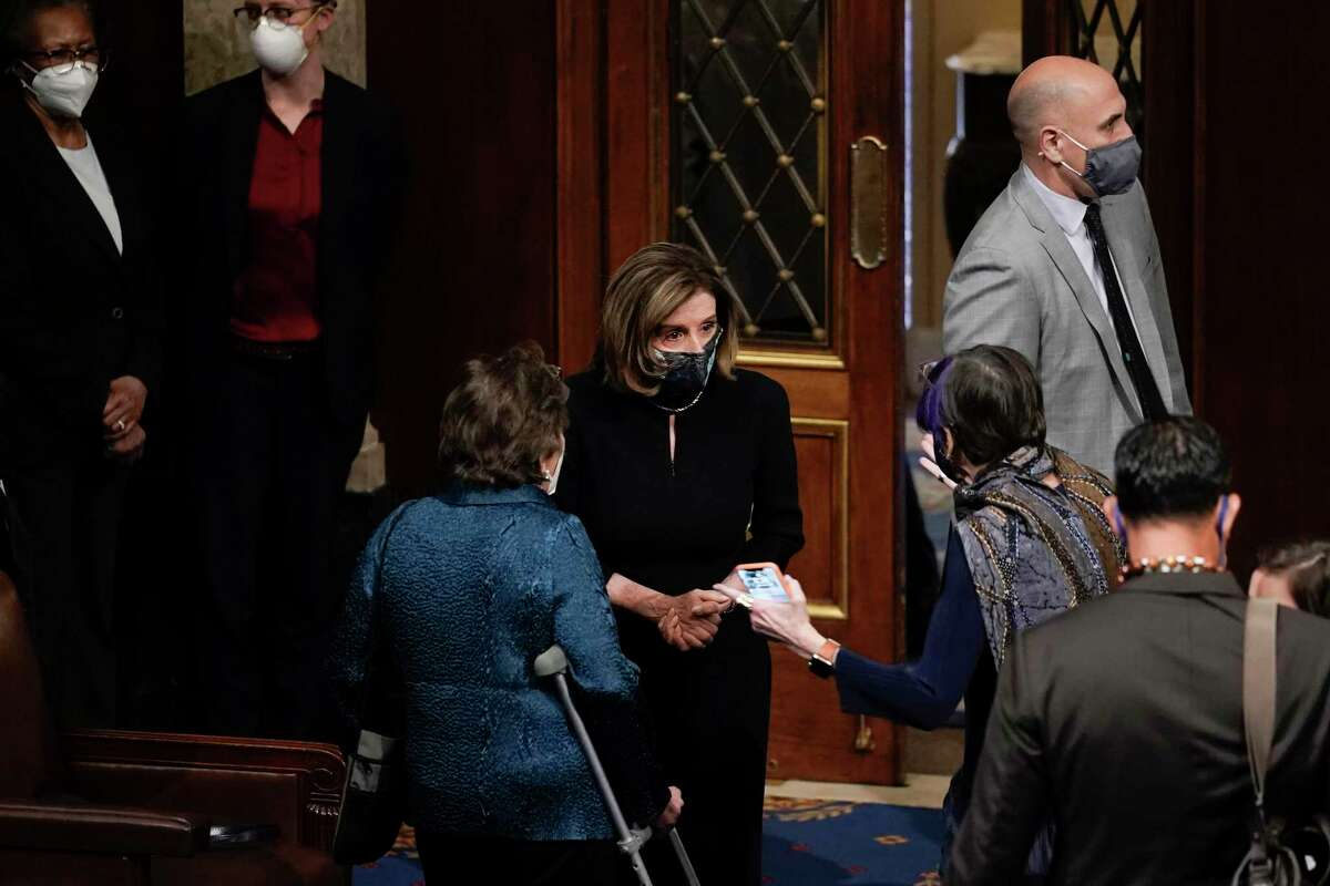 """Speaker of the House Nancy Pelosi, D-Calif., speaks with Rep. Rosa DeLauro, D-Conn., after the U.S. House voted to impeach President Donald Trump in Washington on Wednesday. Trump is charged with """"incitement of insurrection"""" over the deadly mob siege of the Capitol in a swift and stunning collapse of his final days in office.(AP Photo/J. Scott Applewhite)"""