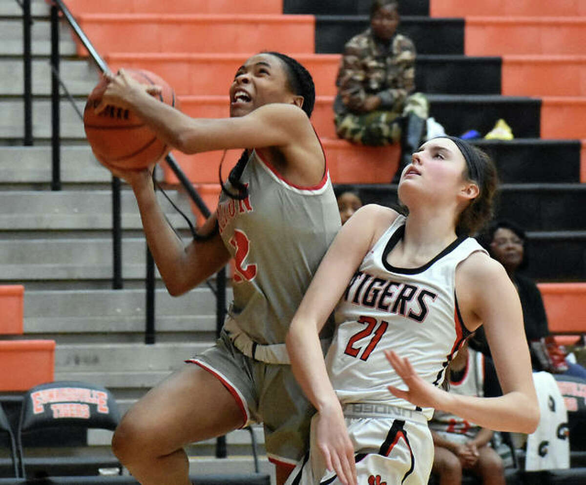 Alton's Germayia Wallace (left) takes the ball to the basket against Edwardsville's Elle Evans during a Jan. 24 game last season at Edwardsville. Wallace, who averaged 15.7 points a game as a junior, sits and waits on the fate of her senior season with the Redbirds.