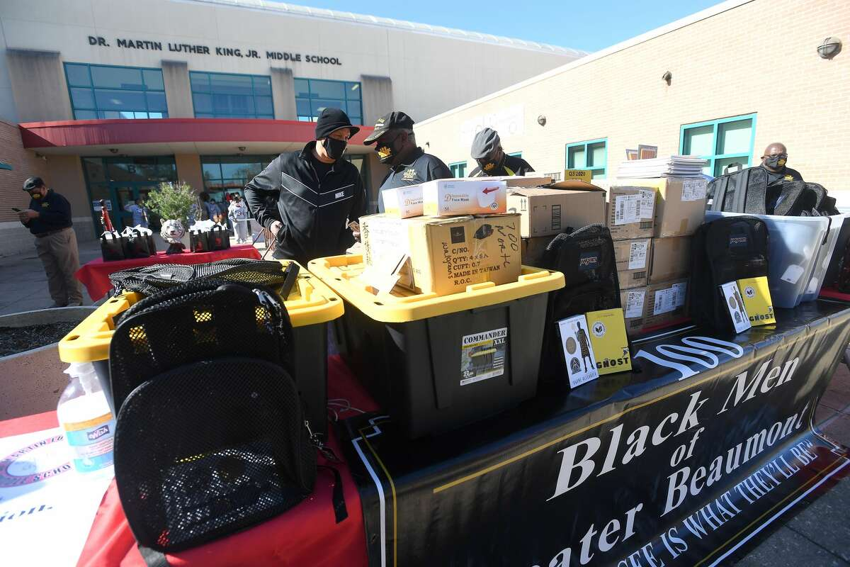 Members of 100 Black Men of Greater Beaumont gather with students and administrators outside of Martin Luther King, Jr., Middle School Wednesday for a celebratory donation of needed school supplies. Hundreds of notebooks, pencils, face masks, and 76 backpacks stuffed with two award winning novels -