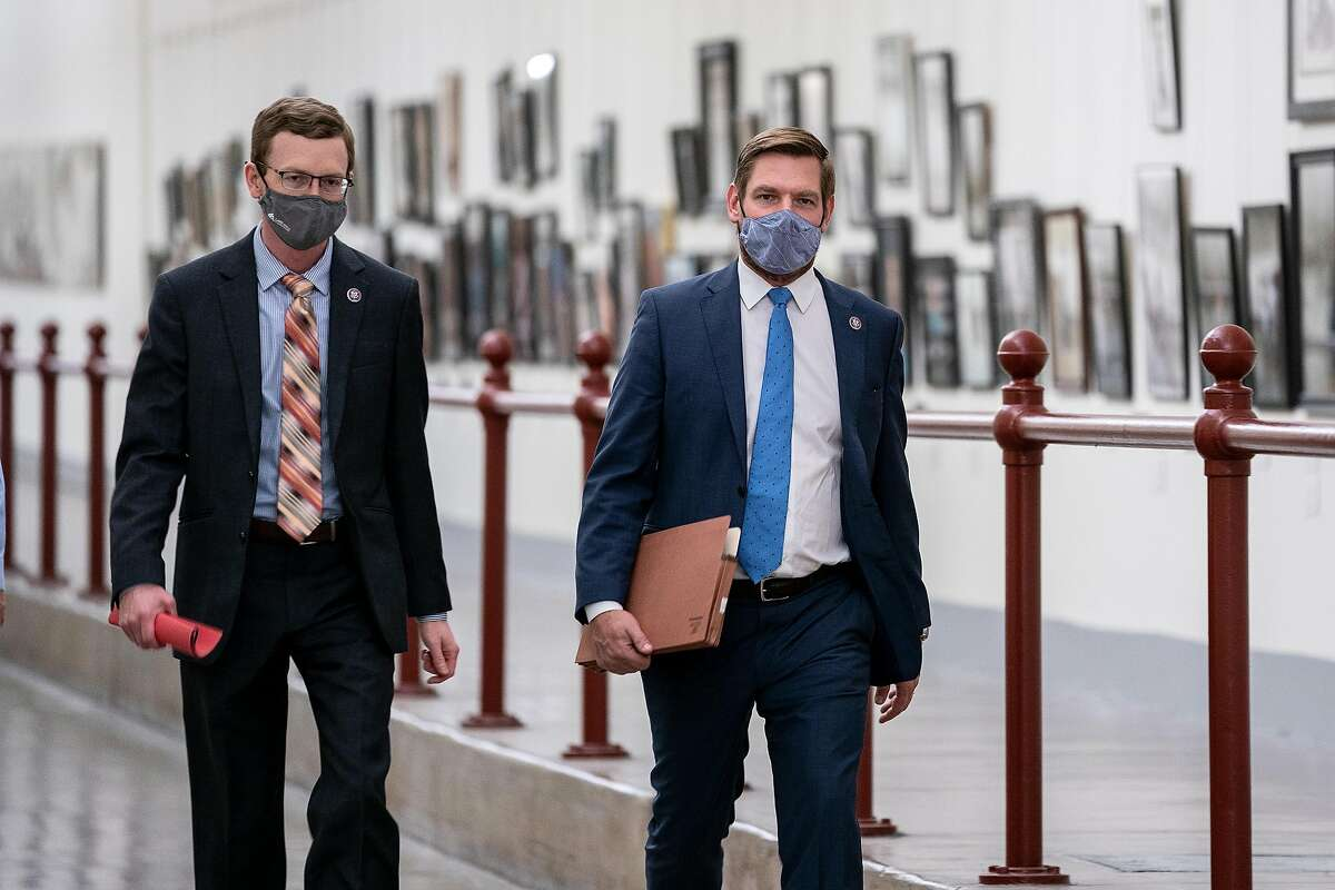 WASHINGTON, DC - JANUARY 12: Rep. Dusty Johnson (R-SD) (L) and Rep. Eric Swalwell (D-CA) wear protective masks while walking through the Canon Tunnel to the U.S. Capitol on January 12, 2021 in Washington, DC. Today the House of Representatives plans to vote on Rep. Jamie Raskin's (D-MD) resolution calling on Vice President Mike Pence to invoke the 25th Amendment, removing President Trump from office. On Wednesday, House Democrats plan on voting on articles of impeachment. (Photo by Stefani Reynolds/Getty Images)