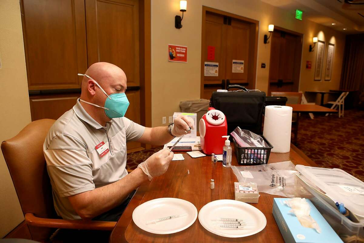 Mike Ring, a CVS pharmacy employee, adds a dose of the Pfizer COVID-19 vaccine into a syringe at Stoneridge Creek on Wednesday, January 13, 2021, in Pleasanton, Calif. Stoneridge Creek, a retirement community, has a 760 resident population and since Monday, 752 of them have been inoculated over a three-day period.