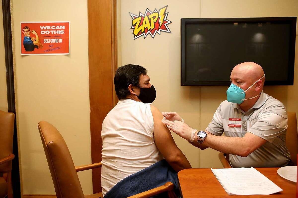 Arnold Fernandez, who works with retirees, receives a shot from Mike Ring at a CVS in Pleasanton.