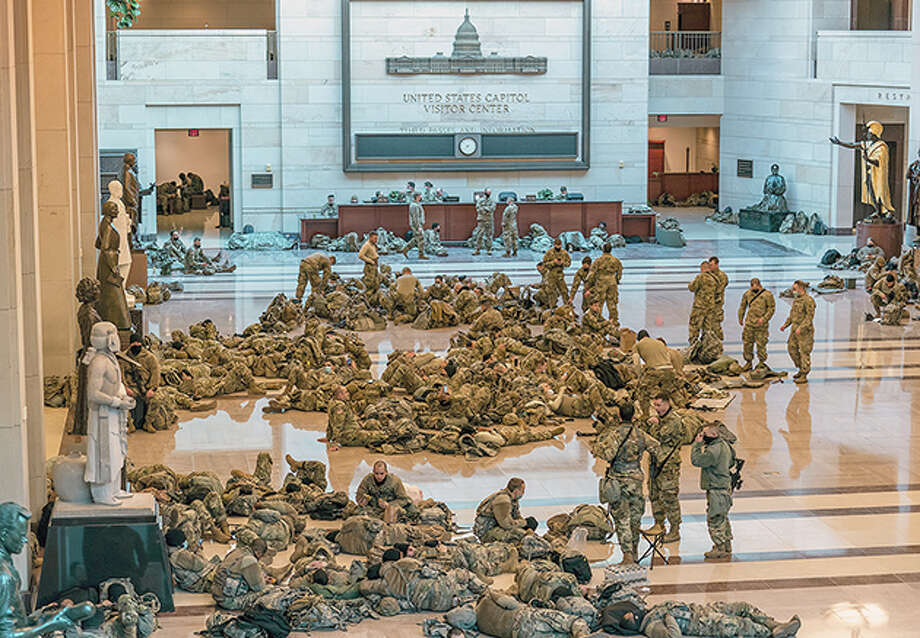 Hundreds of National Guard troops wait Wednesday inside the Capitol Visitor's Center to reinforce security at the U.S. Capitol in Washington, D.C., as the House of Representatives pursued an article of impeachment against President Donald Trump. Photo: J. Scott Applewhite   AP / Copyright 2021 The Associated Press. All rights reserved