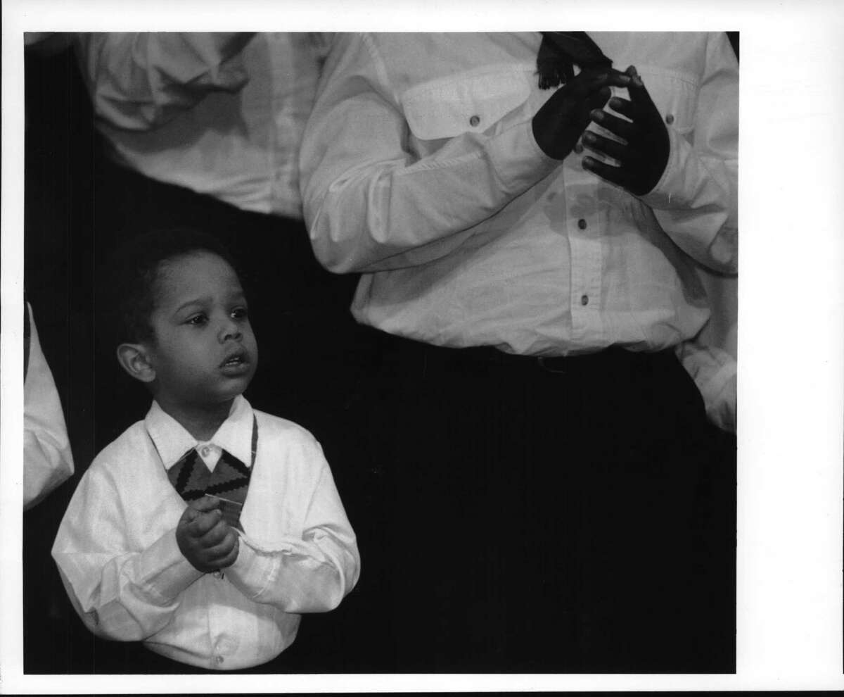 Plaza Convention Center, Albany, New York - Dayshawn Mojica, 3, of Schenectady, sings with the Capital District Mass Youth Choir oat the Martin Luther King day ceremony. January 13, 1993 (Skip Dickstein/Times Union Archive)