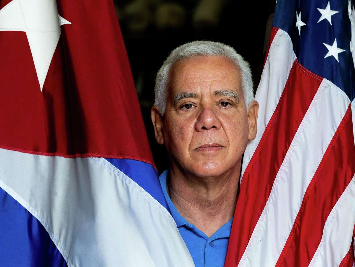 Renier Suárez poses with the Cuban and United States flags Friday, Jan. 8, 2021, in Houston. Suarez is a Cuban American business owner who was against the Cuban government for what he called its authoritarianism and is upset with President Trump for inciting Wednesday riot in the Capitol.