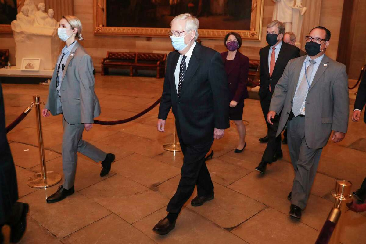Senate Majority Leader Mitch McConnell, R-Ky.., walks in the Capitol early Jan. 7, 2021, hours after a mob riot against Congress.