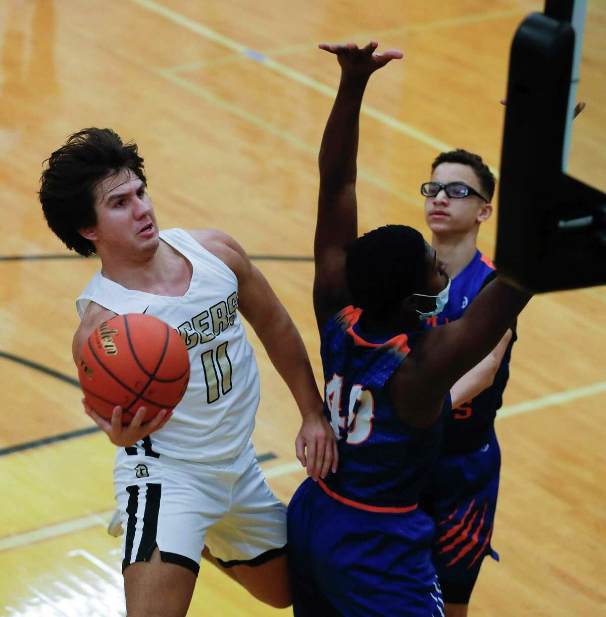 Conroe's Layne O'Dell (11) scoops the ball around Grand Oaks' Ahmad Smith (40) during the first quarter of a District 13-6A high school basketball game at Conroe High School, Wednesday, Jan. 13, 2021, in Conroe.