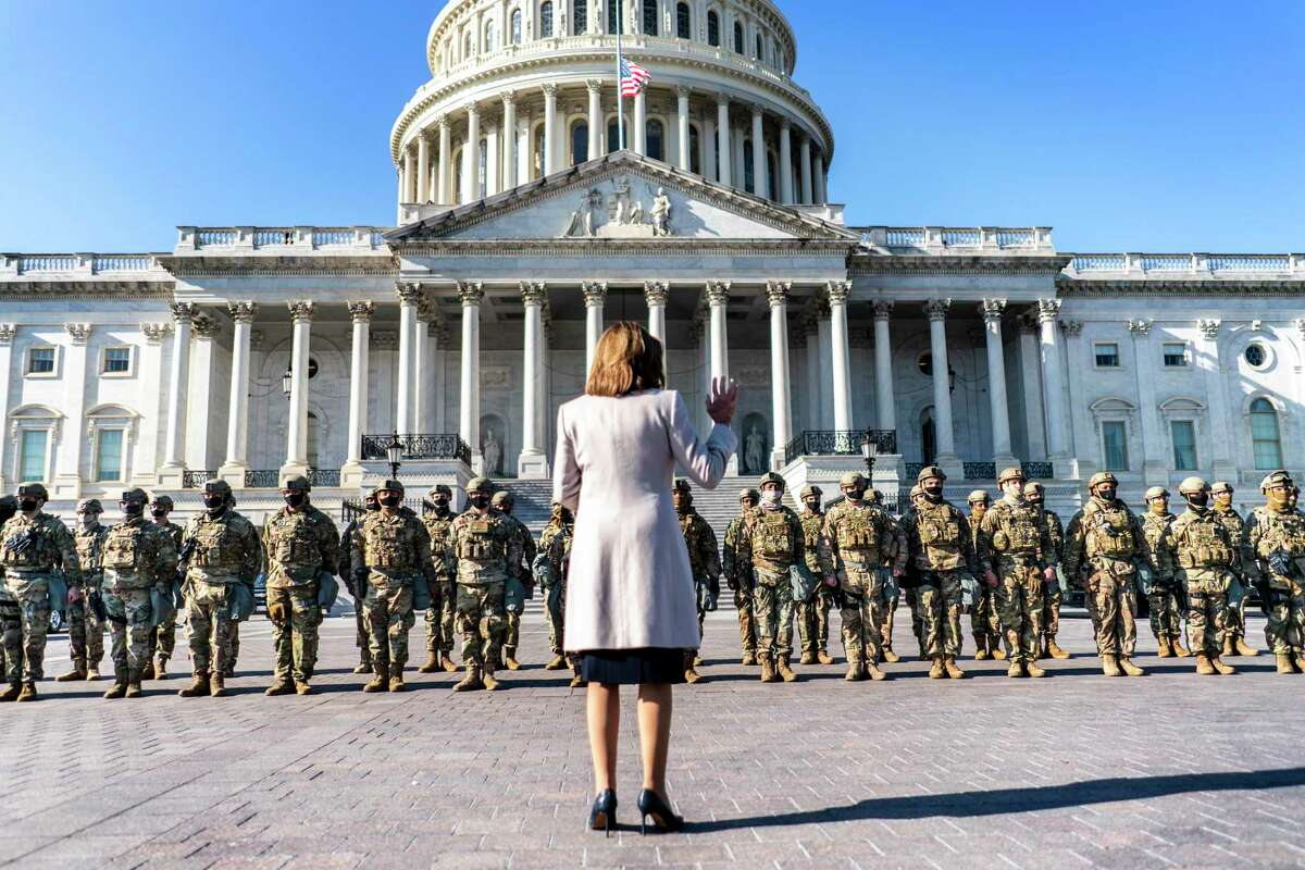 House Speaker Nancy Pelosi greets the National Guard troops occupying and surrounding the newly fenced-in Capitol Complex in Washington on Wednesday.