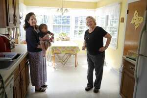 Mary Giordano, left, executive director of Family Promise of the Capital Region and a member of the Shrine Church of Our Lady of the Americas, and Becky Marvin, a Family Promise board member and a member of B'nai Sholom Reform Congregation, pose for a photo in the kitchen of the Family Promise Day Center on Tuesday, Sept. 19, 2017, in Albany, N.Y. Giordano holds Tyrone, 2, a Family Promise guest. (Paul Buckowski / Times Union)