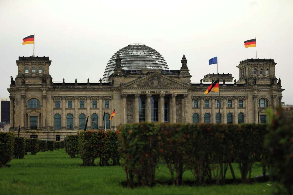 German national flags fly at the Reichstag building in Berlin on Oct. 8, 2020.