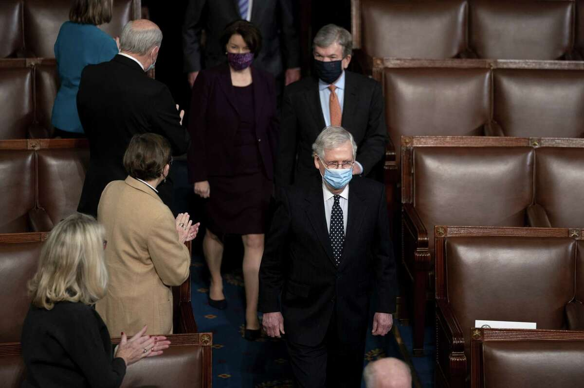Senate Majority Leader Mitch McConnell, a Republican from Kentucky, wears a protective mask while arriving to a joint session of Congress to count the Electoral College votes of the 2020 presidential election in the House Chamber in Washington on Jan. 6, 2021.