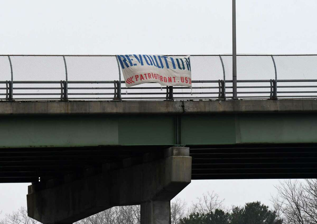 A sign attributed to a white supremacist group is displayed above I-90 at Exit 6 on Thursday, Jan. 14, 2021, in Albany, N.Y. Law enforcement took the sign down Thursday afternoon. (Will Waldron/Times Union)
