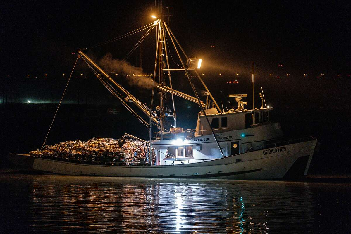 A crab fishing boat loaded with crab pots heads out to sea as the first catches of the season arrive in San Francisco on Wednesday.