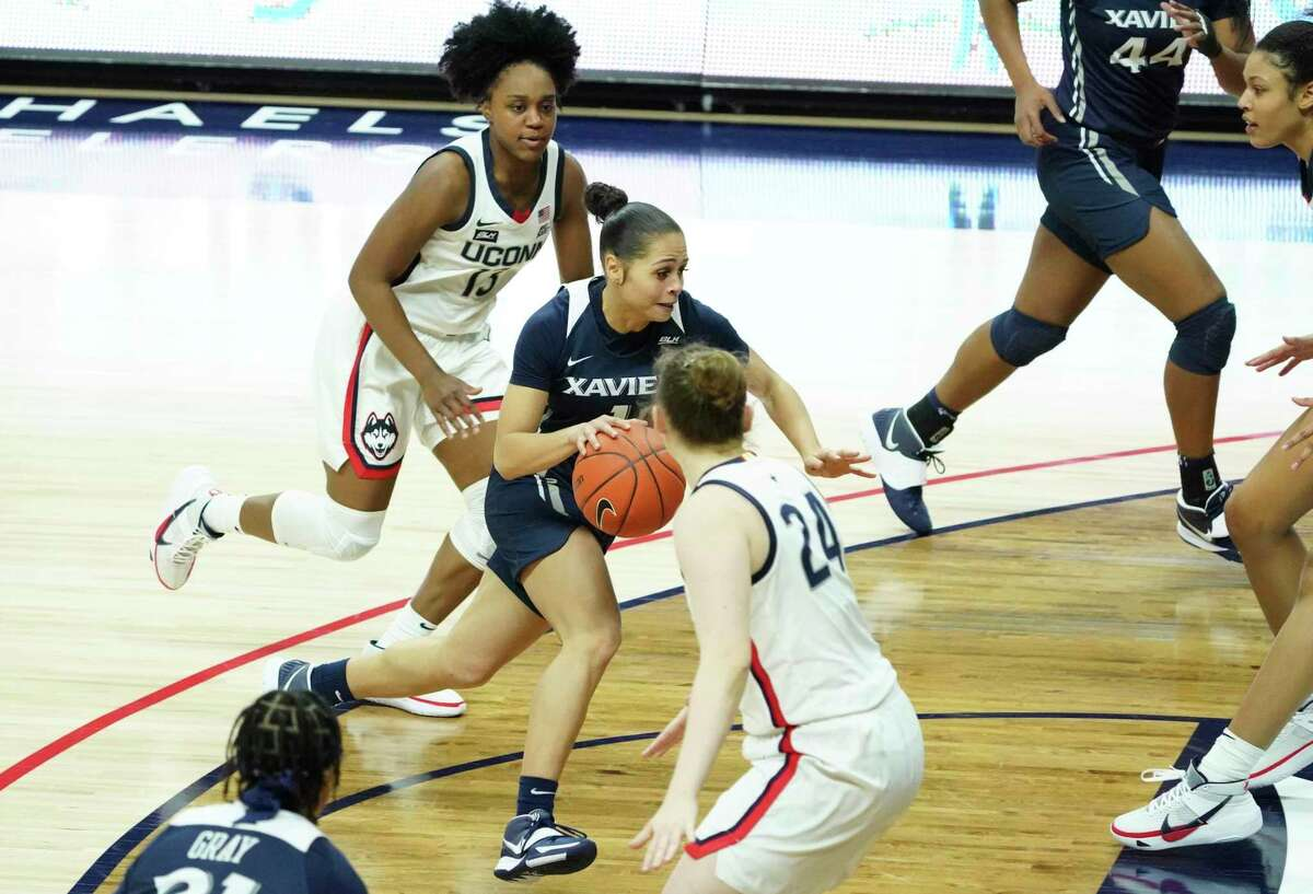 Xavier's Nia Clark (1) drives to the basket while defended by UConn's Christyn Williams (13) and Anna Makurat (24) on Dec. 19 in Storrs.